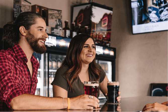 Two happy young people enjoying a beer